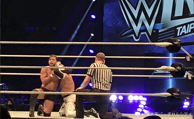 WWEのロゴをバックにシン・カラと戦うHIEO ITAMI
